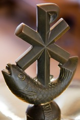 A fish and a Roman cross, two of the oldest Christian symbols. They are seen here on top of the font used for baptisms in St. Philips' Cathedral, Birmingham.