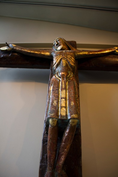 Close up of a heavily stylised modern crucifix hanging over a small side chapel altar in St. Philips' Cathedral, Birmingham.