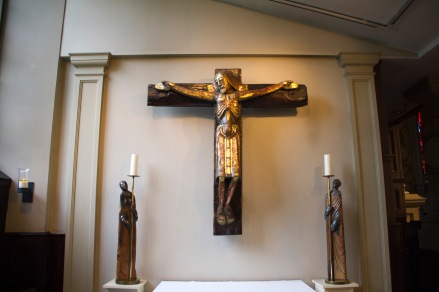 A heavily stylised modern crucifix, with supporting candle holders, hangs over a small side chapel altar in St. Philips' Cathedral, Birmingham.