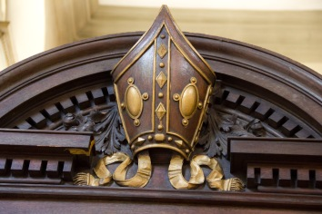 """This carved Bishop's hat signifies that the seat below is the Bishop of Birmingham's seat at St. Philips' Cathedral, Birmingham. This important chair has a connection to the meaning of the word """"cathedral"""" itself. The Latin for throne is """"cathedra"""", bishops are described as being """"ex cathedra"""" (trans. """"on the throne""""). As such the bishop's chair itself has great importance within the branches of Christianity-like Anglicanism-which have bishops."""