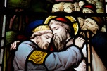 Detail of men embracing in a larger stained glass window at Edgbaston Old Church.