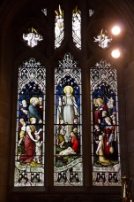 The people, both on earth and in heaven, gather around Jesus. Stained glass window Edgbaston Old Church.