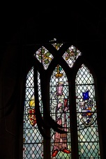 Stained glass window of a saint, with bell pulls in the foreground Edgbaston Old Church.