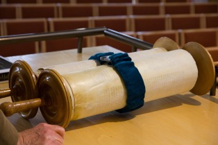 A bound scroll lies upon the lectern in the synagogue.