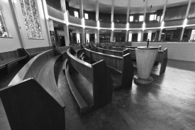 """The pews in Catherine of Sienna Roman Catholic church, central Birmingham, and the church's very simple font for the baptism of infants (and occasionally adults). In common with all Roman Catholic churches built in the mid to late 1960s it is """"in the round"""". This is because it was decided by the Vatican II church council that the Roman Catholic church as an organisation should be more and inclusive of ordinary believers and allow all to participate in services on equal terms."""
