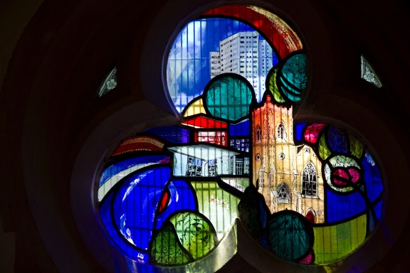 Close up of a contemporary stained glass window at St. John's Church, Ladywood. With the high-rises in the background, trees and shrubs in the foreground at the church itself in the middle, it symbolises that St. John's stands at the heart of the inner-city community that it serves.