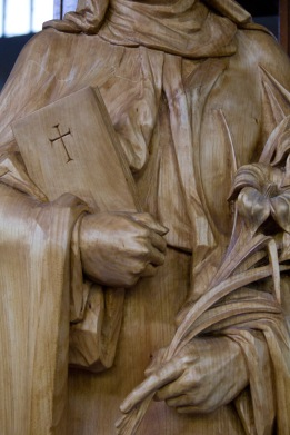 Close up of a holy book in the arms of a carved wooden statue of May the Mother of Jesus standing in the Catherine of Sienna Roman Catholic church, central Birmingham.