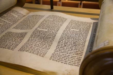 A close up of a scroll written in Hebrew script.
