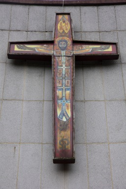 A brightly painted modern crucifix on the outside of the Catherine of Sienna Roman Catholic church, central Birmingham.