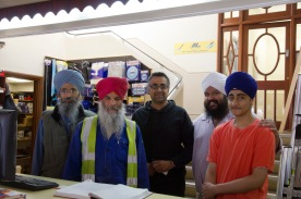 Workers behind the counter at the Gudwara's hardwear shop.