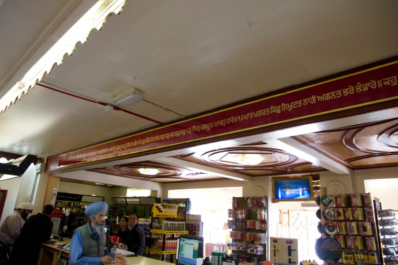 Customers stand at the counter of the Gudwara's in-house hardwear shop