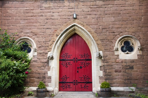 The, large, solid, rather imposing; main door of St. John's Church, Ladywood. It is flanked by carvings on either side.