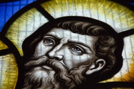 Close up of a face in a modern stained glass window showing the disciples watching Jesus ascend to heaven. It is in St. Catherine of Sienna Church, central Birmingham.