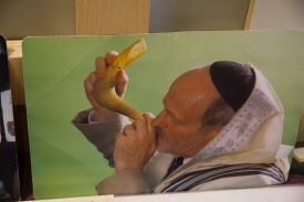 A picture of a man in religious garb blowing a shofar.