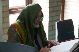 A man reading a book in the library and study space of Birmingham Central Mosque.