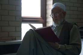 A man reading in a book in the library and study space of Birmingham Central Mosque.