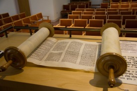A religious scroll, written in Hebrew, rests upon the synagogue's lectern.