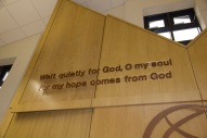 A sacred phrase intended to help worshipers reflect. It is also written in Hebrew on the other side of the sanctuary.