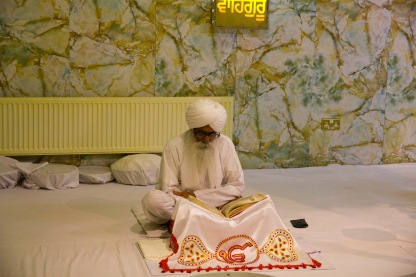 A man reads from scripture during worship at the Gudwara.