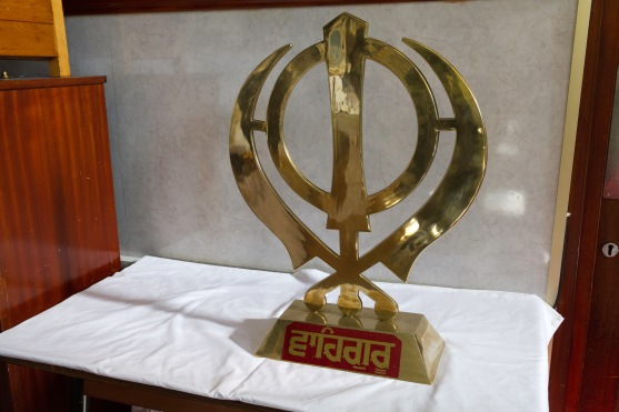 A small golden Khanda sitting on an altar. The Khanda is the primary symbol of Sikhism, it signifies divine knowledge and God's holy perfection.