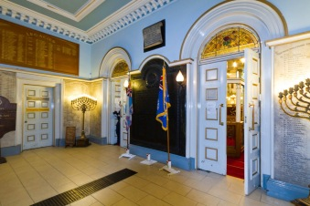 The entrance hall to Singers Hill synagogue in central Birmingham. Note the war memorial to those from the community who died in World War I alongside traditional Jewish religious artifacts like the Menorah.