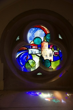 A contemporary stained glass window at St. John's Church, Ladywood. With the high-rises in the background, trees and shrubs in the foreground at the church itself in the middle, it symbolises that St. John's stands at the heart of the inner-city community that it serves.