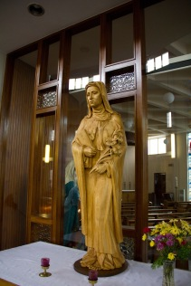A traditional statue of Mary the Mmother of Jesus. It is found in St. Catherine of Sienna Roman Catholic church, central Birmingham. It stands on a small altar and is intended to inspire devotion.
