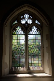 Plain stained glass windows, with light streaming through them, in an alcove of St. John's Church, Ladywood.