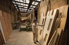 A worker stands by a pile of doors-made on site-for the upkeep of the Gudwara.